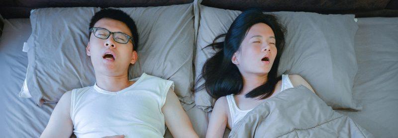 couple sleeping on bed in bedroom, top view